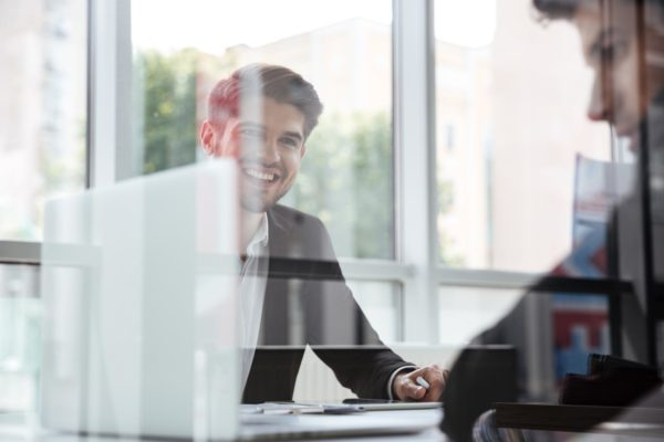 Two cheerful young businessmen with laptop on business meeting in office